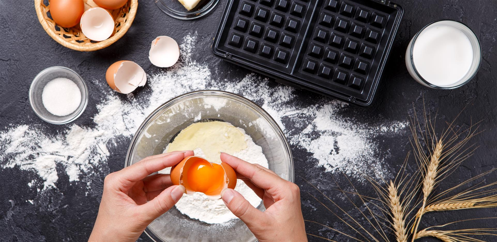 two hands cracking an egg into a bowl. other eggs are cracked and a waffle machine