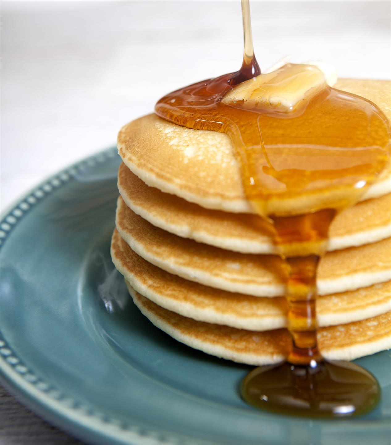 stack of pancakes topped with butter and syrup is being poured on top