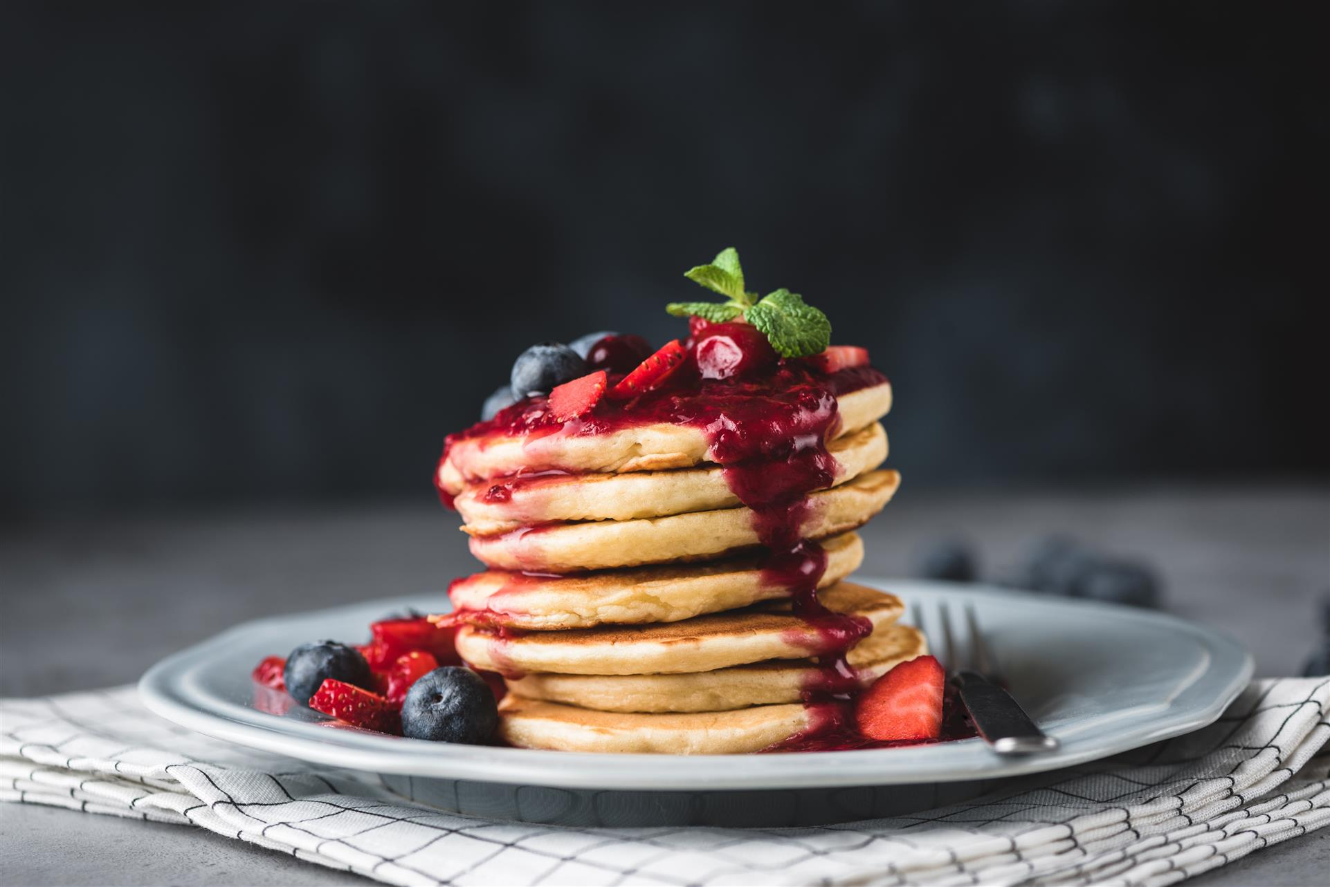 stack of pancakes topped with syrup, blueberries and raspberries