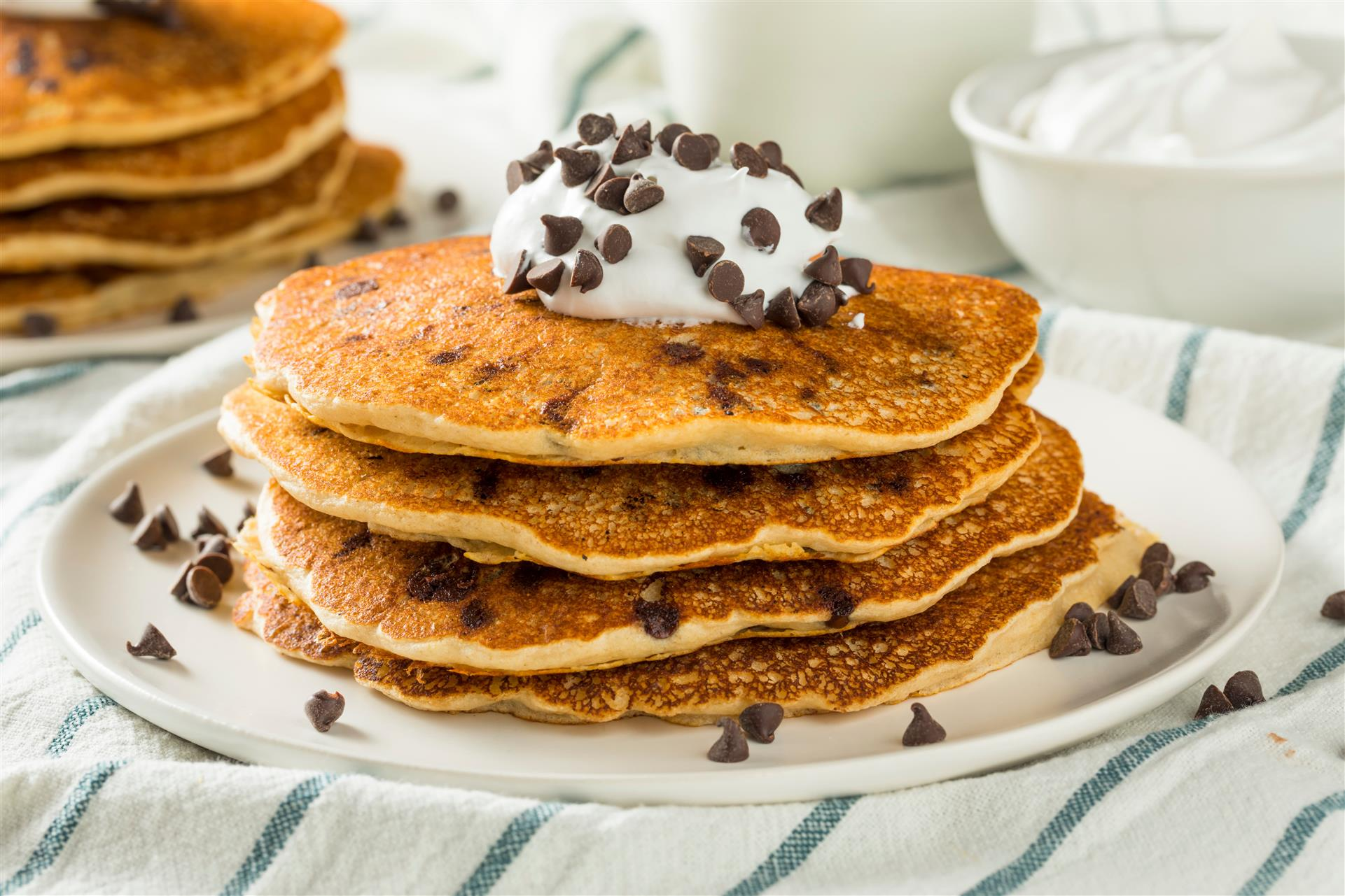 stack of pancakes topped with whipped cream and chocolate chips