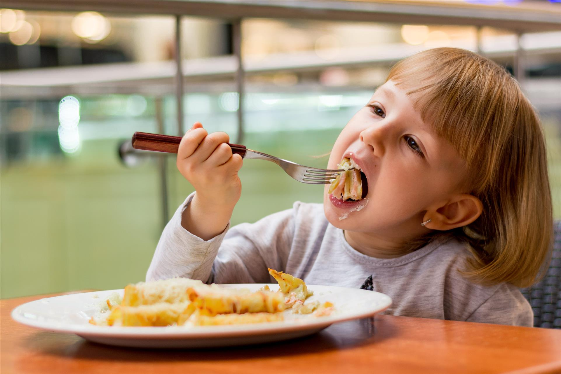 young girl eating at table and putting a piece of pancake in her mouth using a fork
