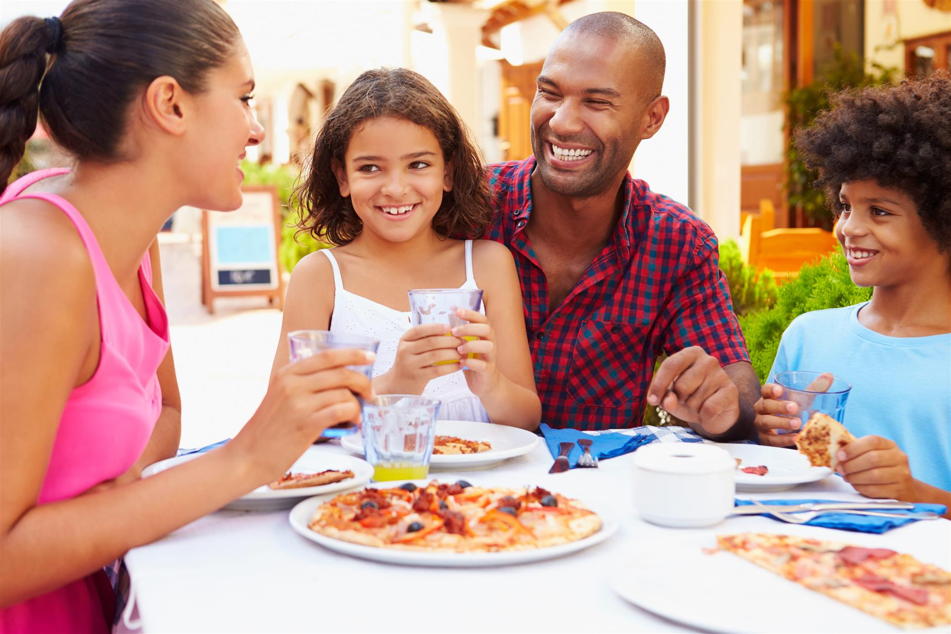 a family of four sitting at a table enjoying a meal