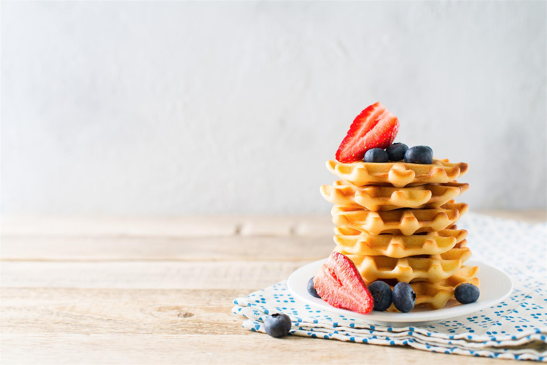 stack of waffles topped with syrup, blueberries and strawberries