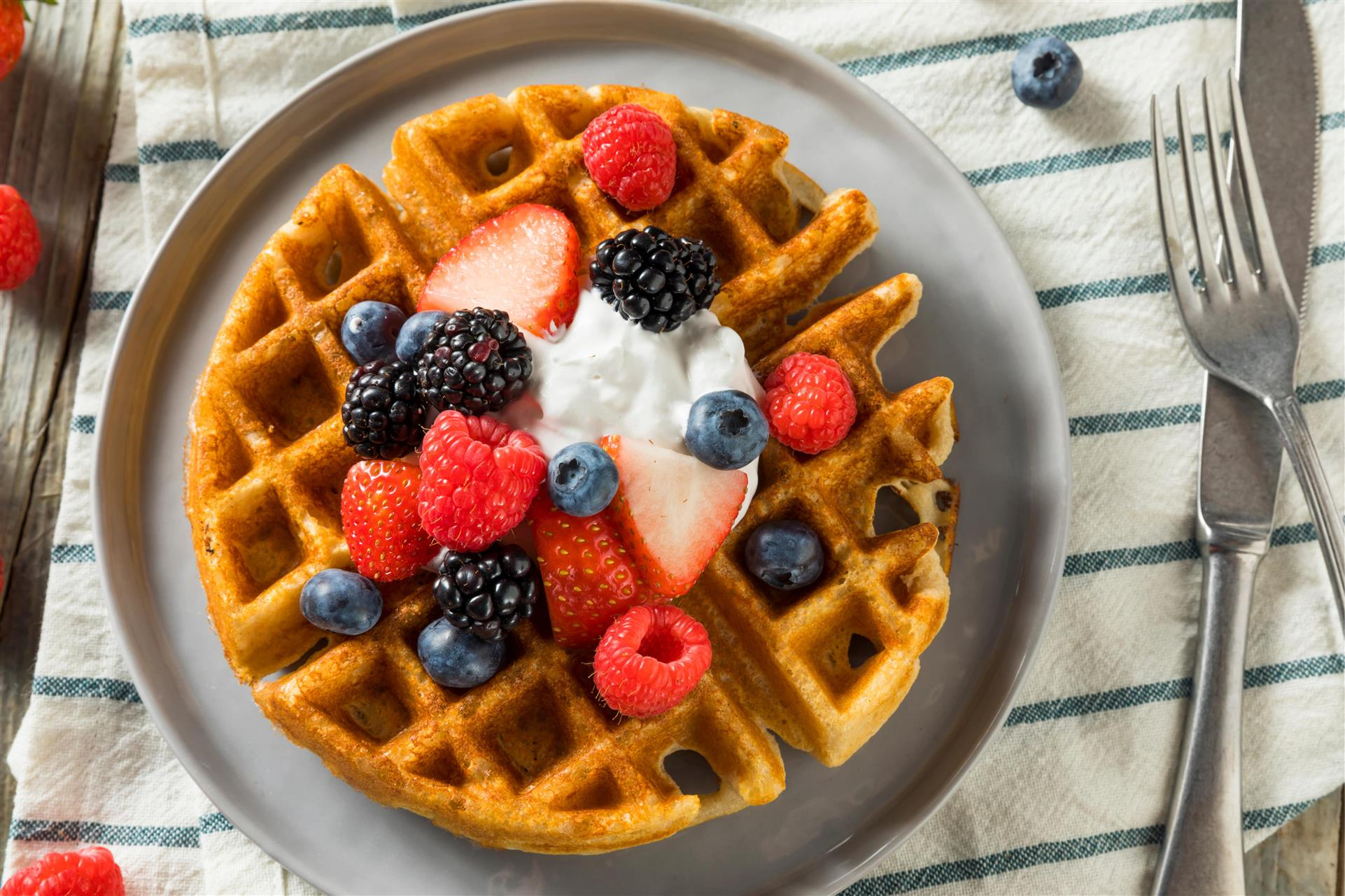 waffle topped with whipped cream, blueberries and raspberries
