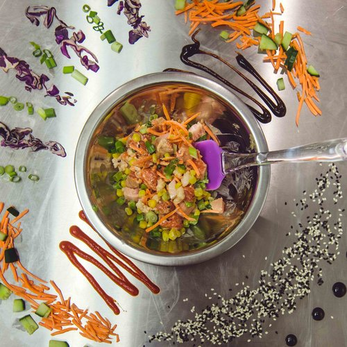 Bowl of sashimi salmon and tuna with shredded carrots with assorted spices on a metal counter-top