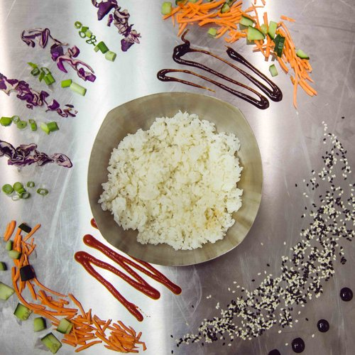 Bowl of white rice with assorted spices on a metal counter-top