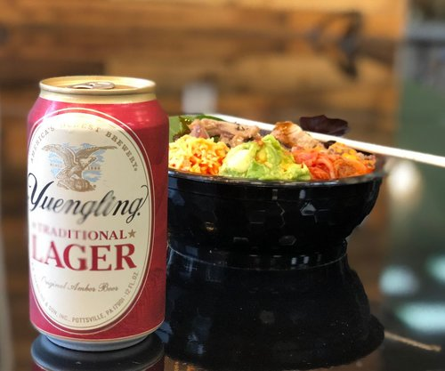 Yuengling lager in a can next to a salmon poke bowl with chop sticks