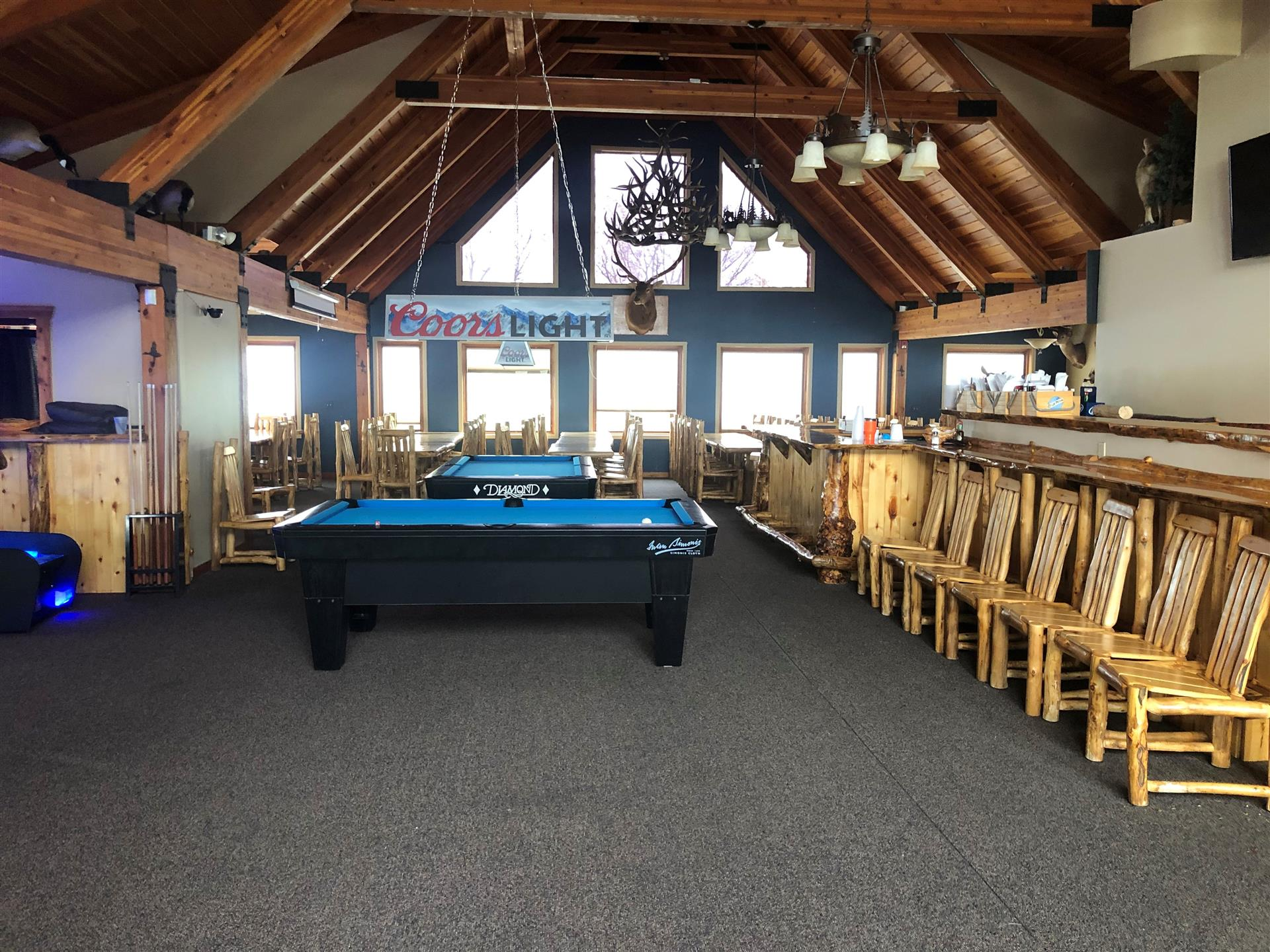 2 pool tables in an open room with wooden tables and chairs around