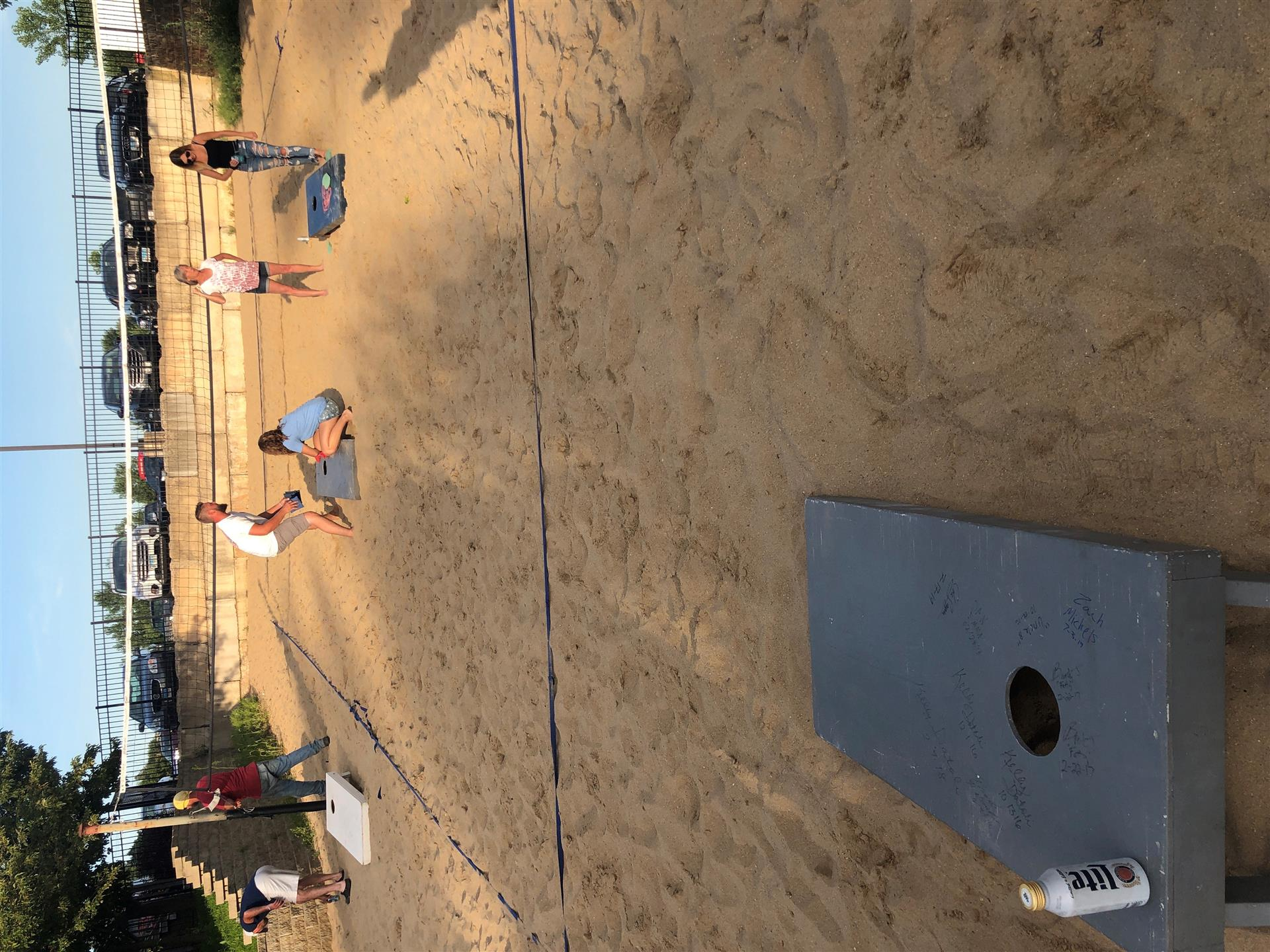 people playing corn hole on a beach volleyball court