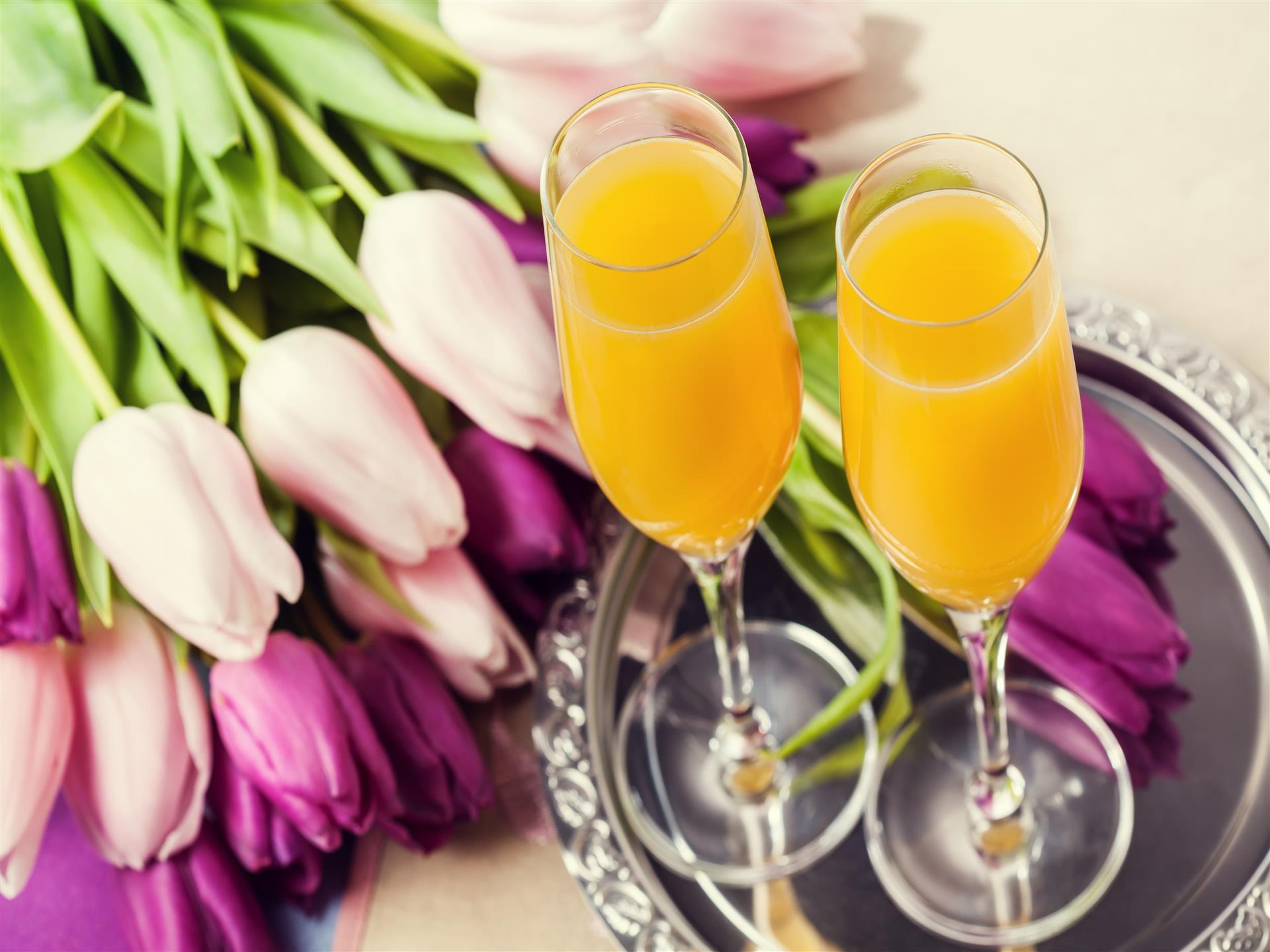 Two mimosas on serving tray next to flowers