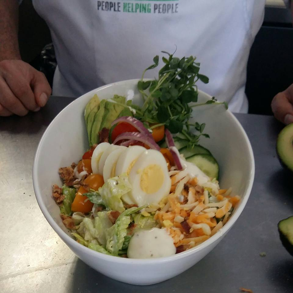 Loaded cobb salad with sliced hard boiled eggs, onions, avocado, cucumbers and cheese