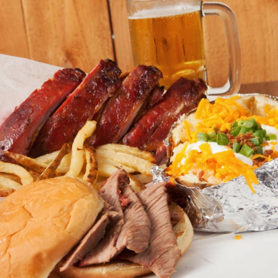Sliced BBQ ribs, brisket sandwich, fries and a loaded baked potato with a glass mug filled with beer