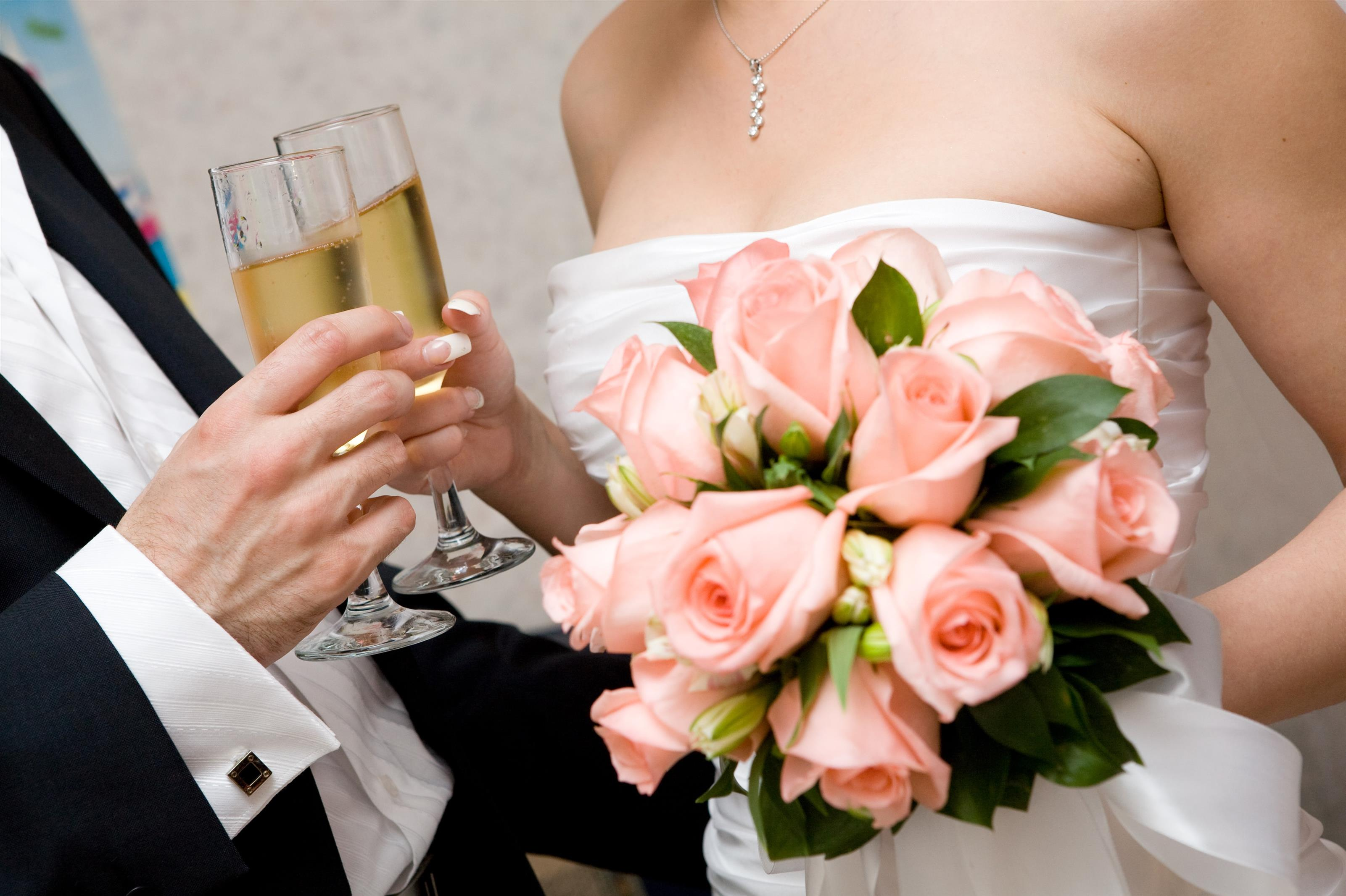 Bride and groom holding champagne glasses and flowers