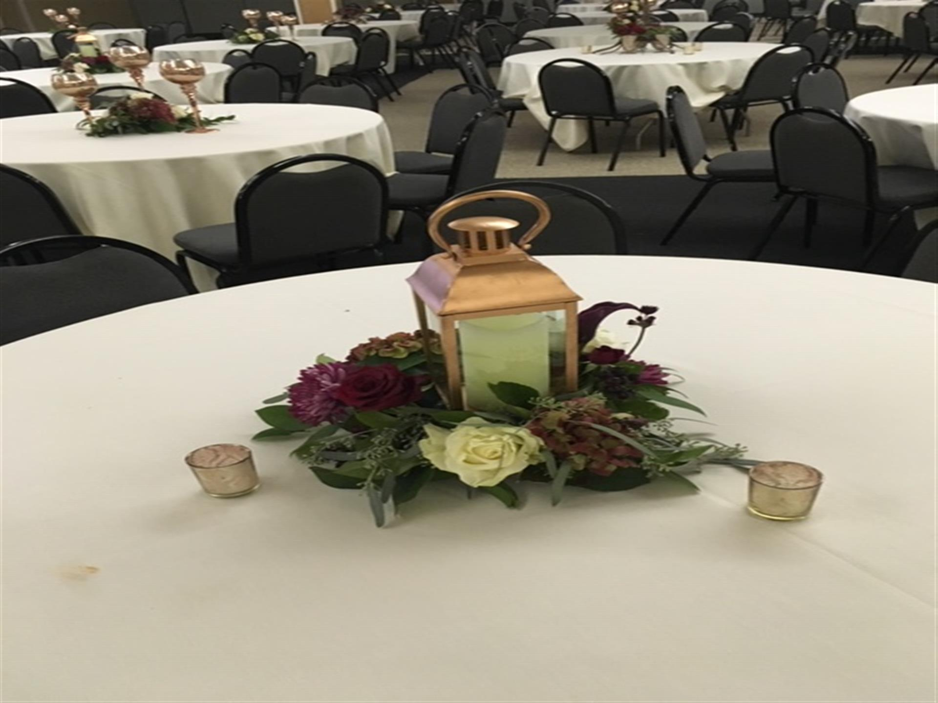 Round table covered in a tablecloth with flower centerpiece  inside Mesenberg Hall