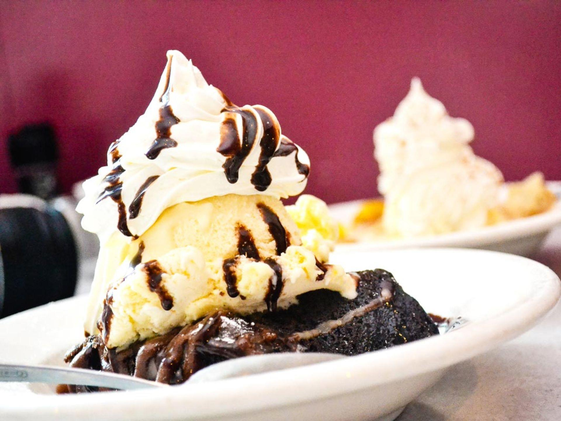 warm brownie dessert topped with ice cream and whipped cream with chocolate syrup