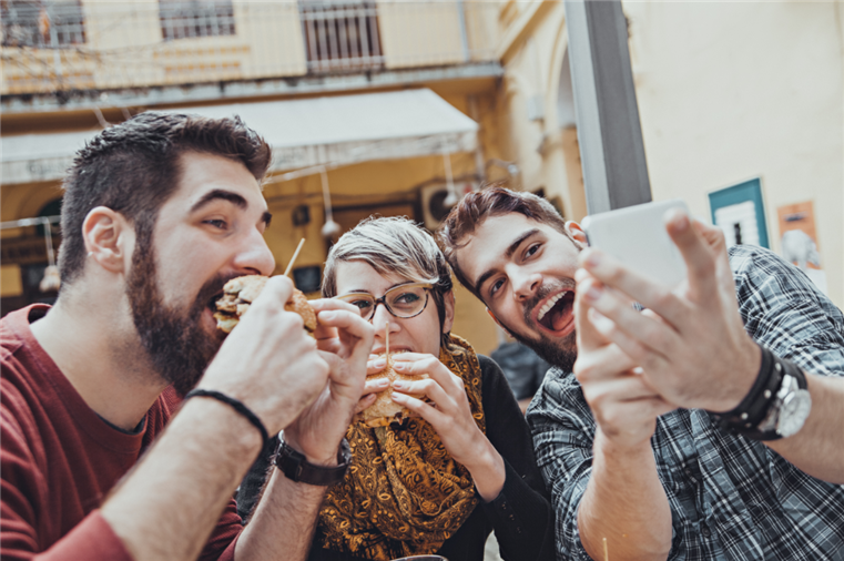 group of people eating burgers while taking selfies