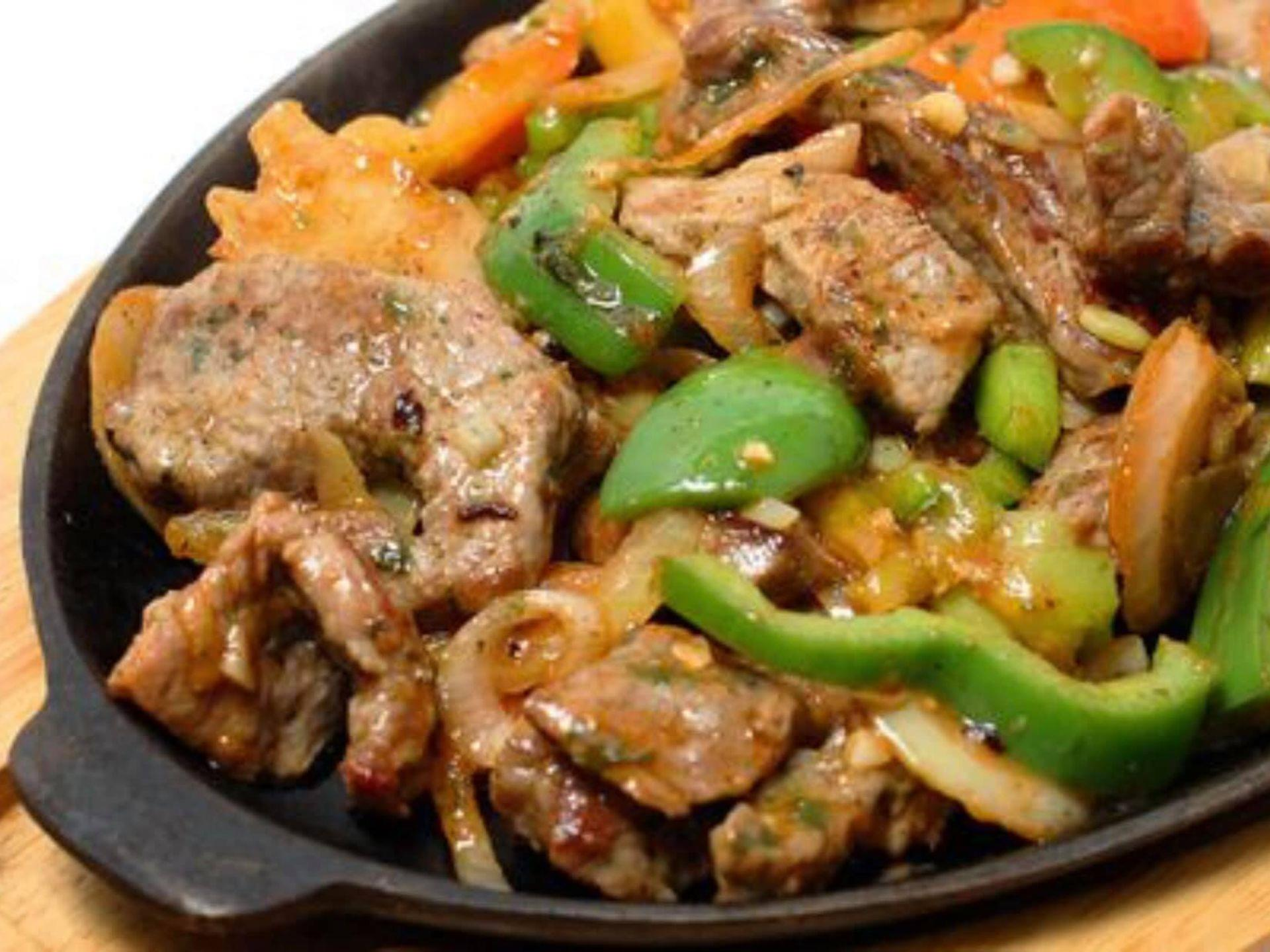 Steak fajitas in a skillet with onions and peppers