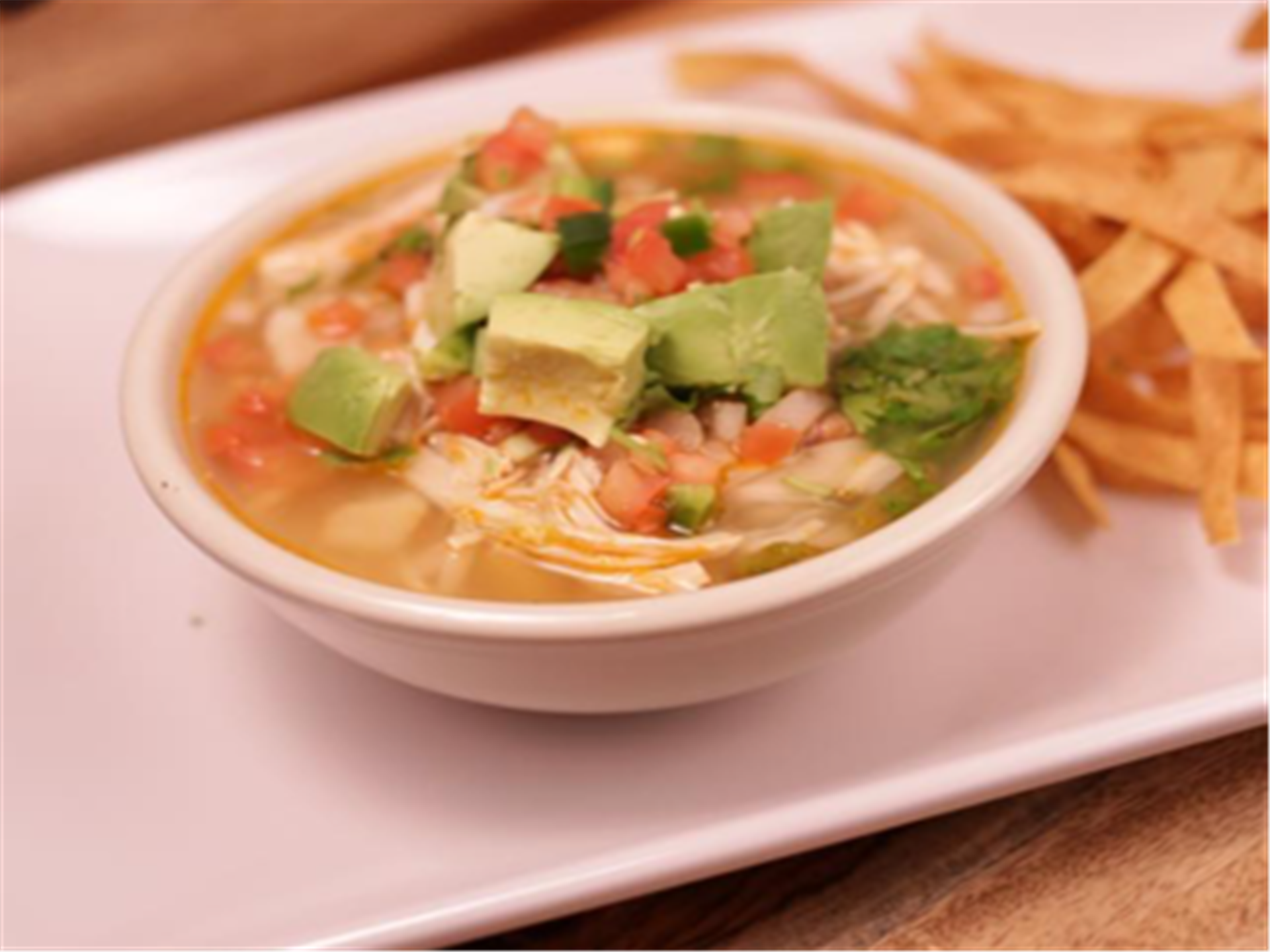 Chicken Soup. A hearty chicken broth layered with flavor. Shredded chicken breast, rice, vegetables, pico de gallo, and avocado. Topped with tortilla strips