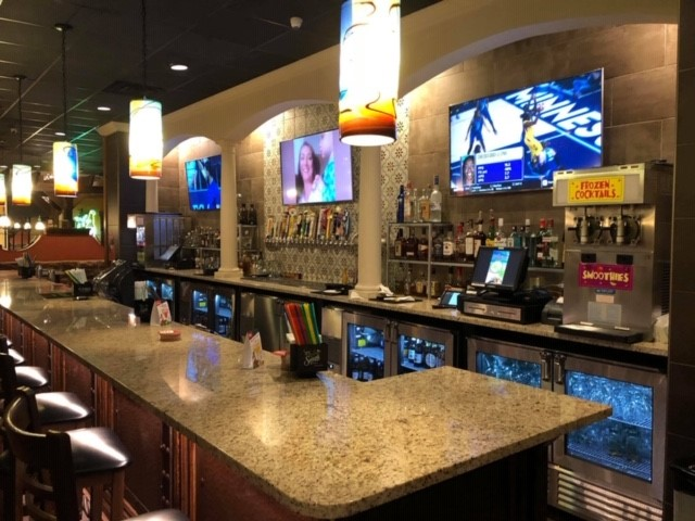 Inside of the bar with three big screen tvs behind it