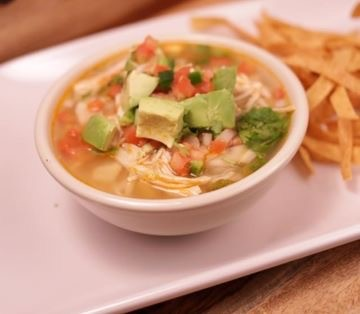 Chicken soup with avocado, tomato and chicken