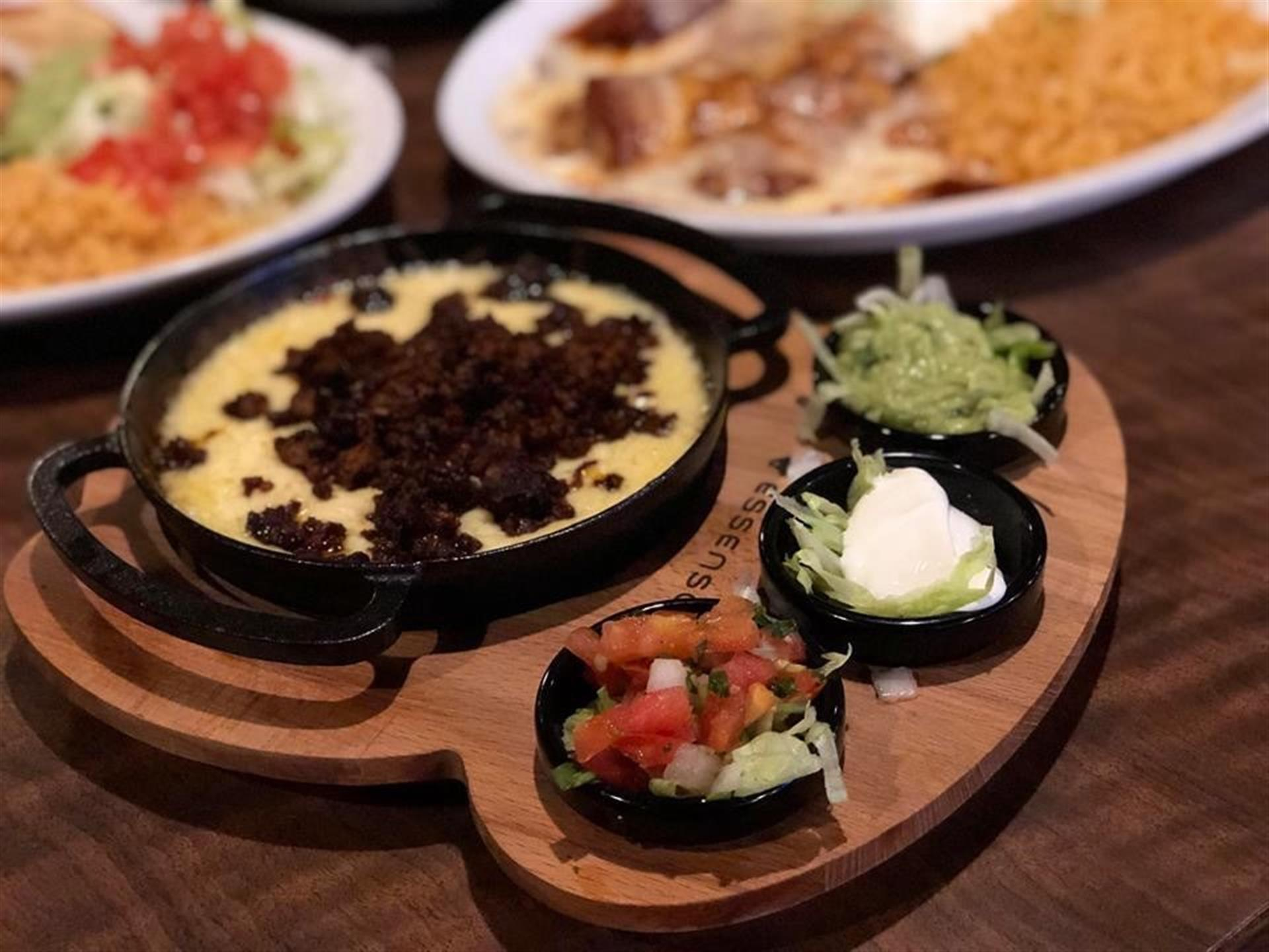 queso in a metal pot with salsa, sour cream and lettuce on the side