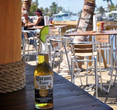 corona bottle with lime wedge on a wooden deck outdoors