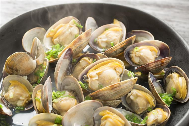 little neck clams opened up with parsley as a garnish