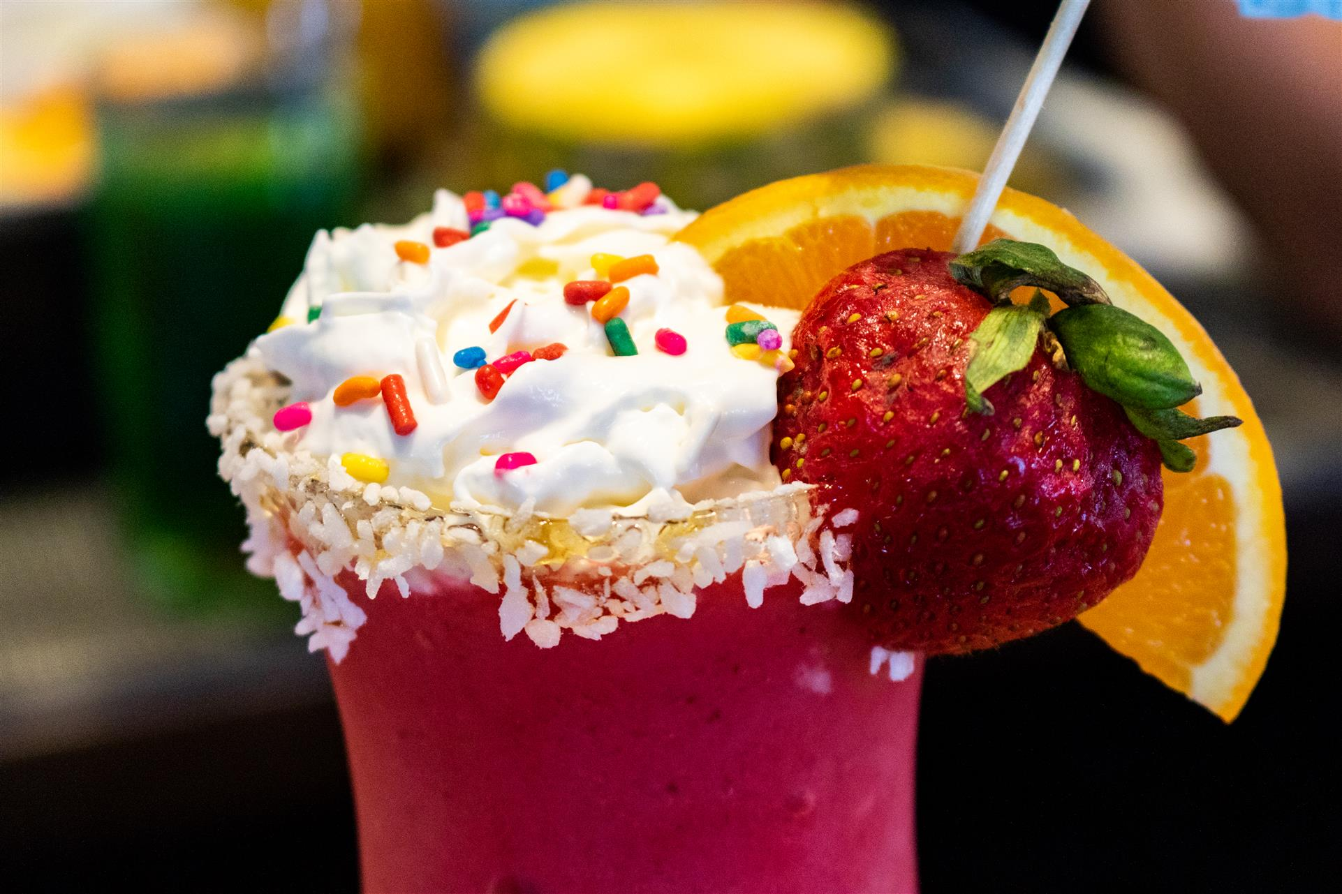 strawberry cocktail with a whole strawberry, whipped cream, sprinkles and an orange wedge