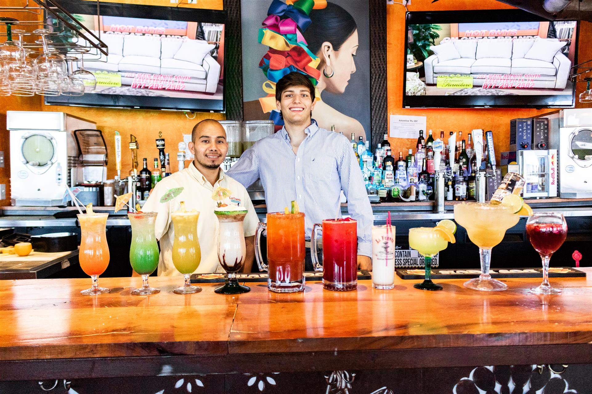 two bartenders smiling behind the bar showcasing all of the restaurants speciality cocktails