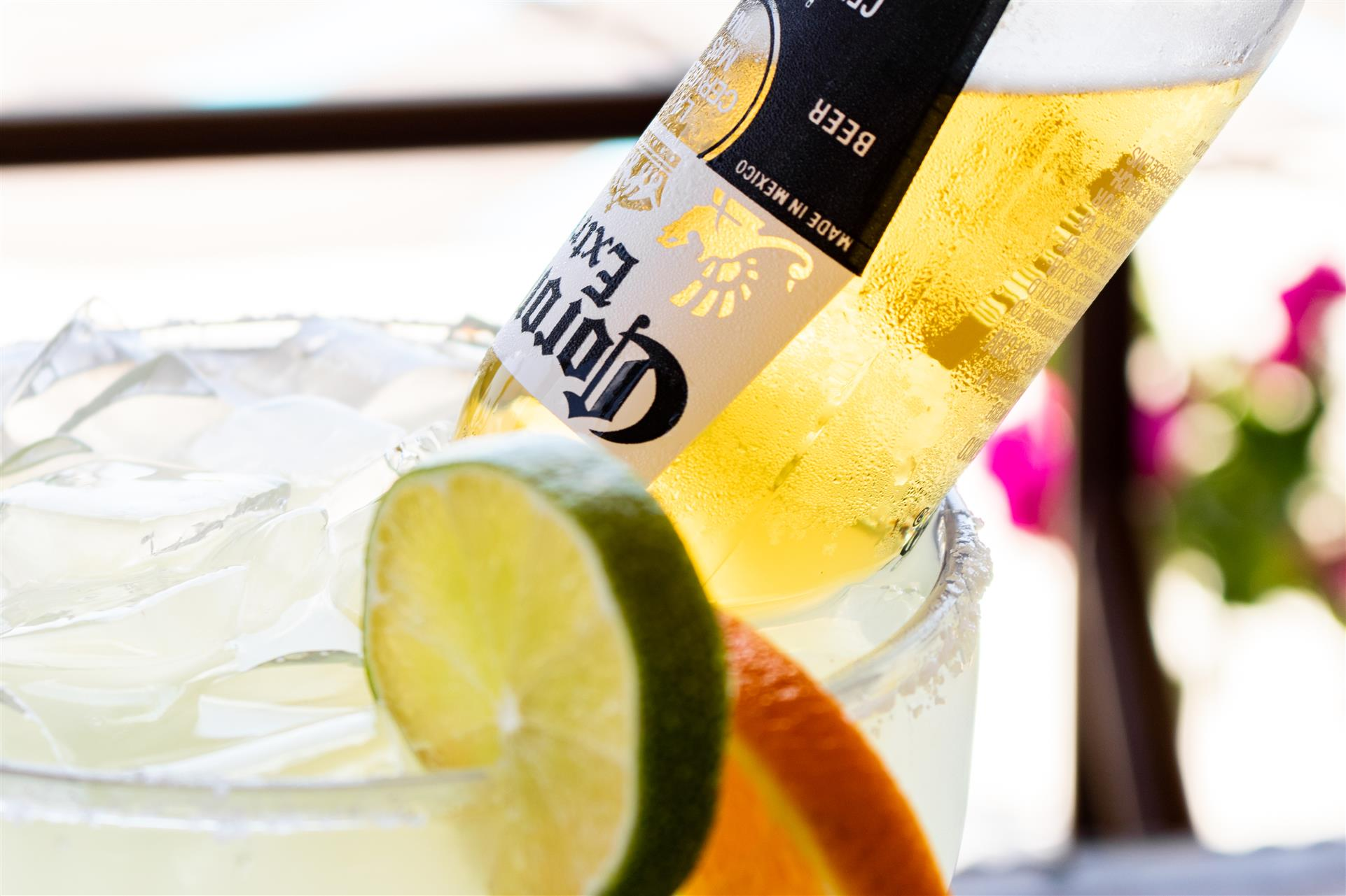 cocktail with an upside down bottle of corona, lime and orange wedges on the side
