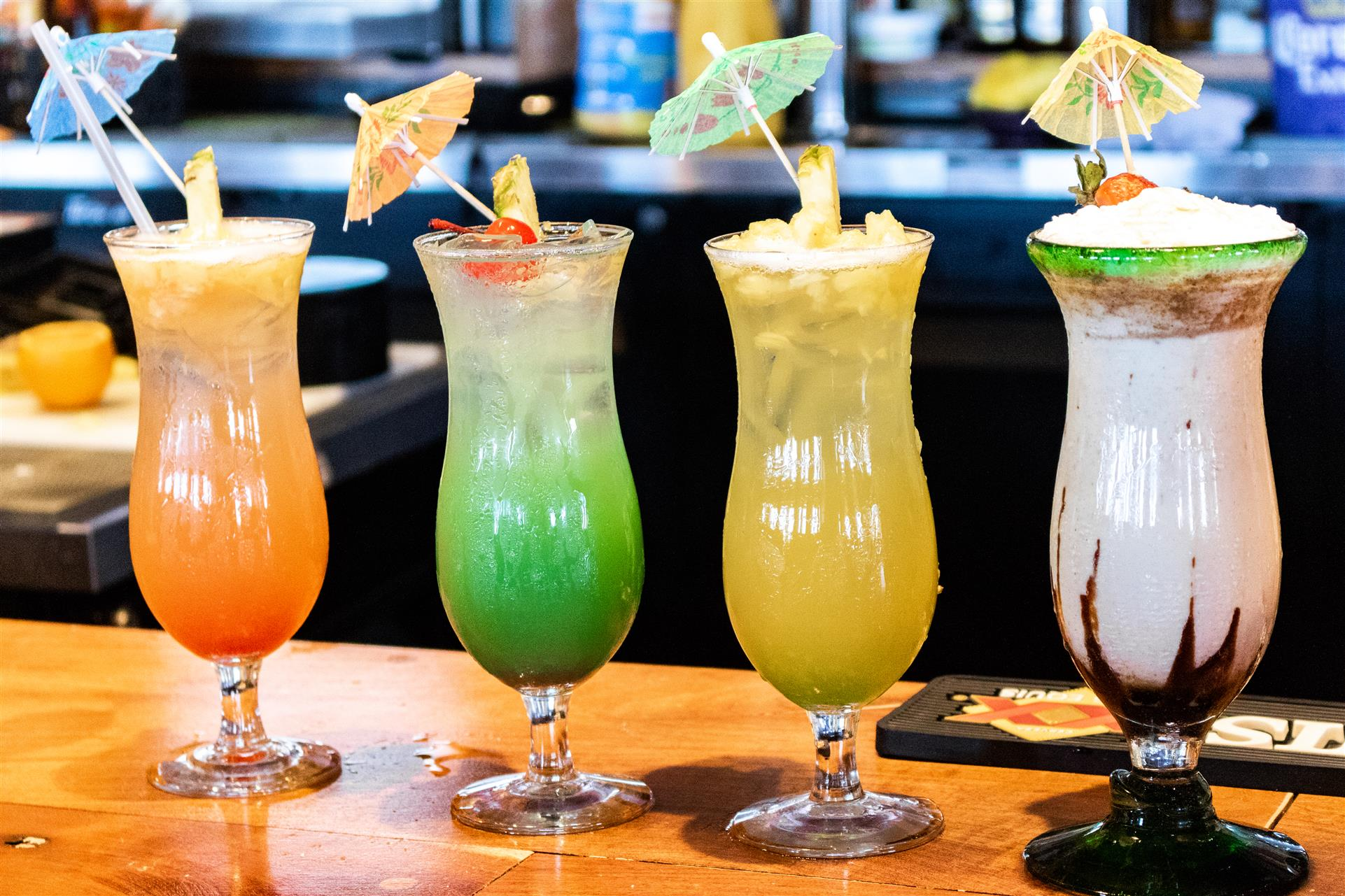 various cocktail drinks with umbrellas being displayed on the bar