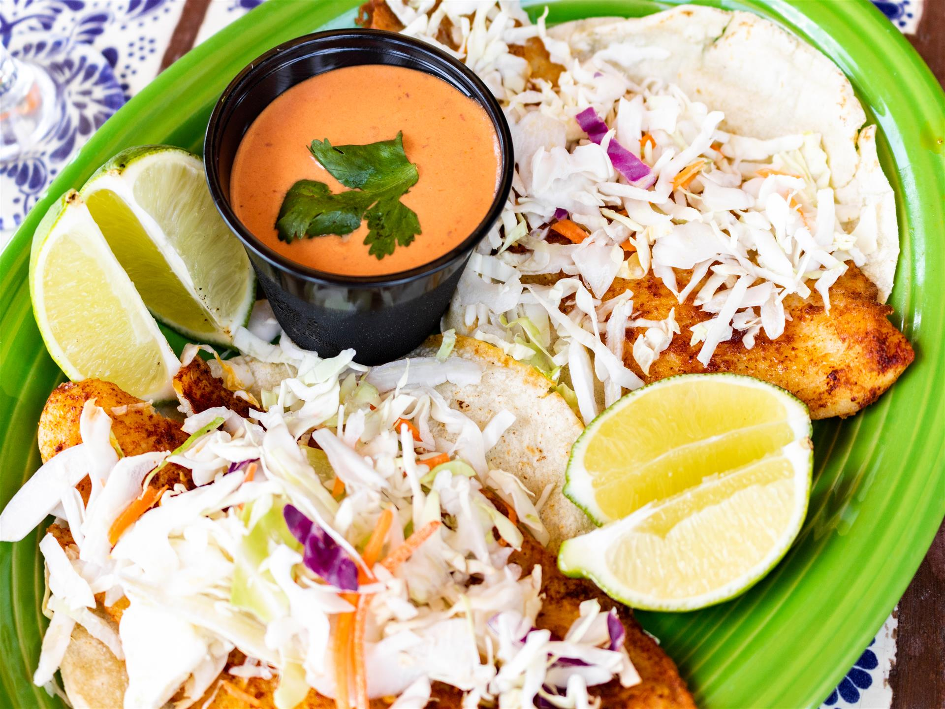 two fish tacos with lime wedges and dipping sauce on the side.