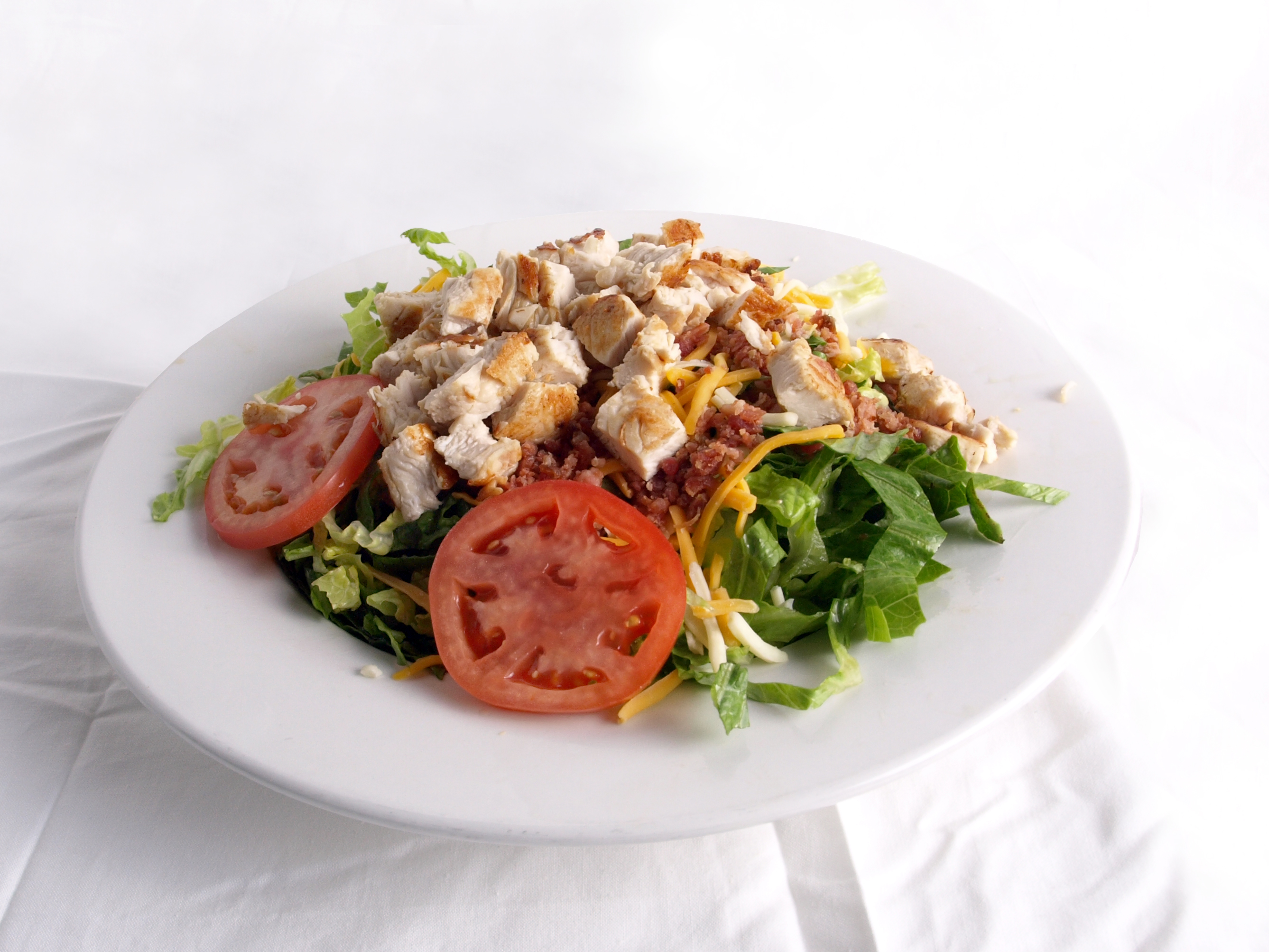 Grilled chicken salad with tomatoes, bacon and cheese