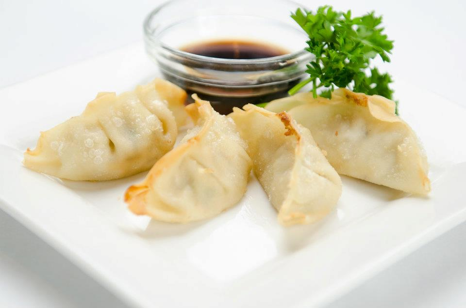 Four pieces of Gyoza (dumplings) with soy sauce
