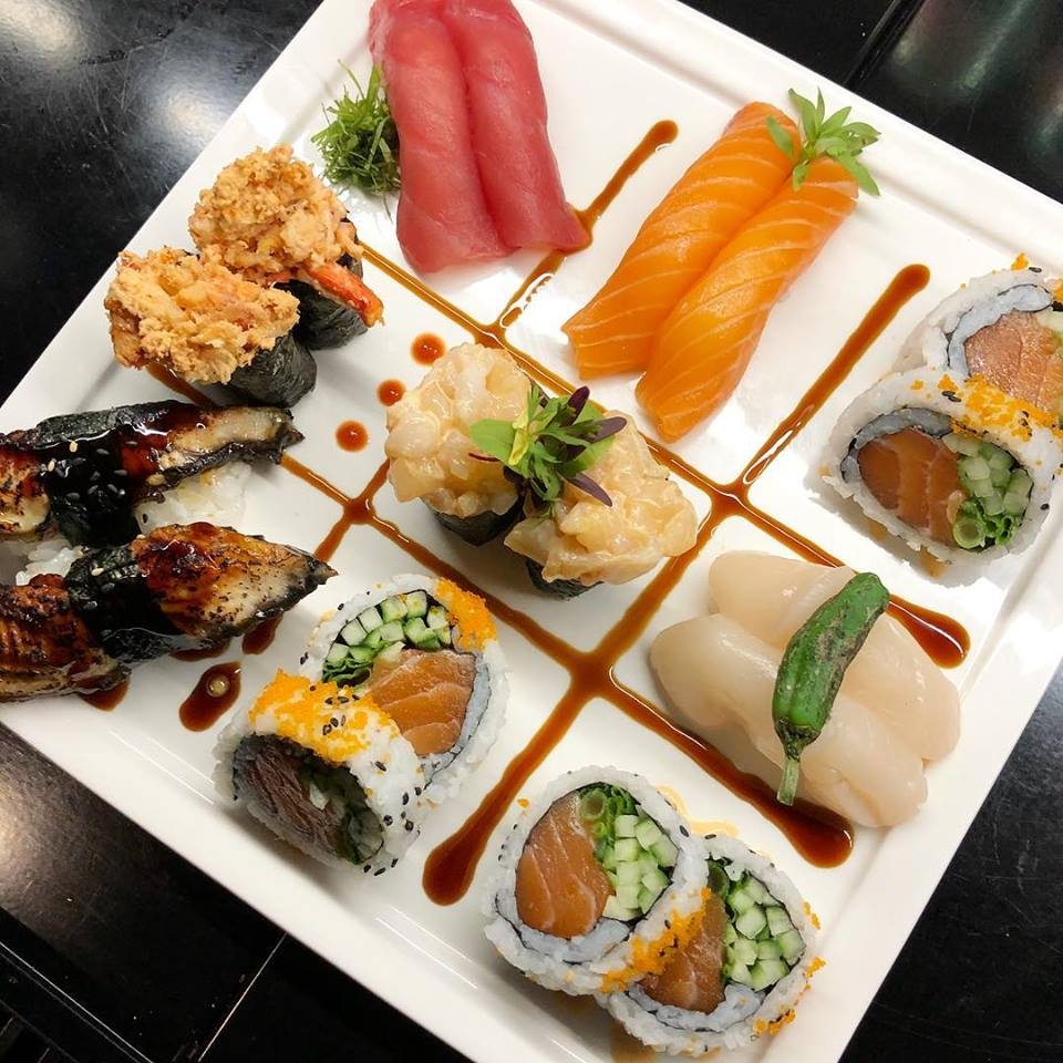 Assorted sushi and sashimi laid out decoratively on dish