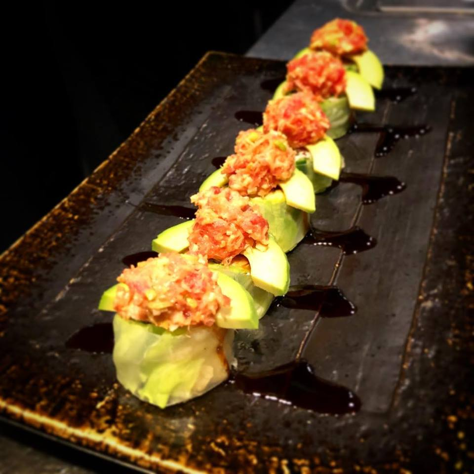 Rice paper roll topped with avocado and spicy tuna .