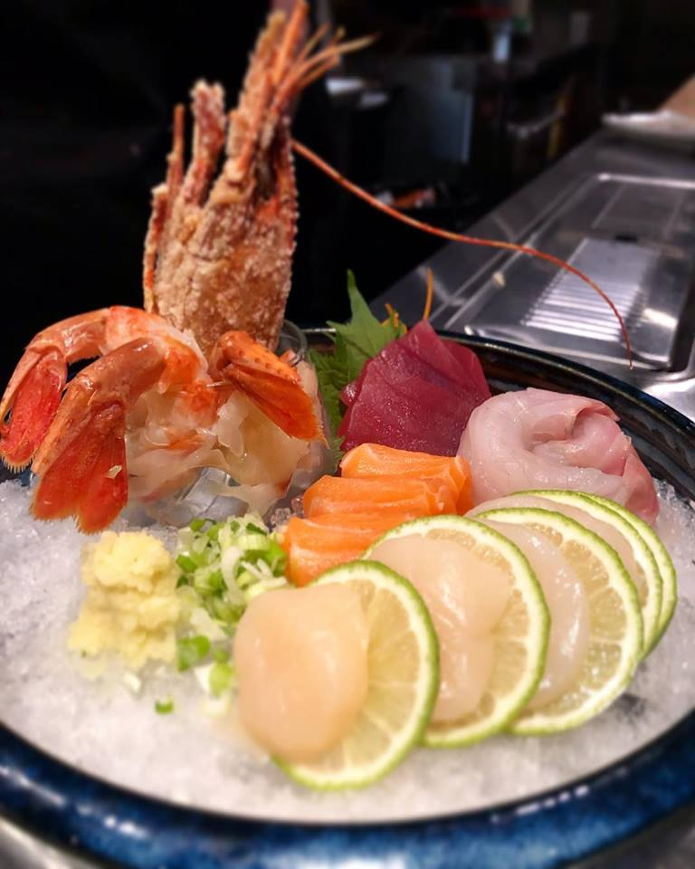 Assorted sashimi and shrimp on crushed ice plate, garnished with limes