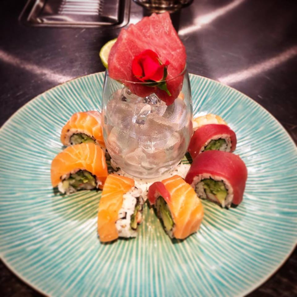 Sashimi in glass of ice on dish surrounded by sushi rolls