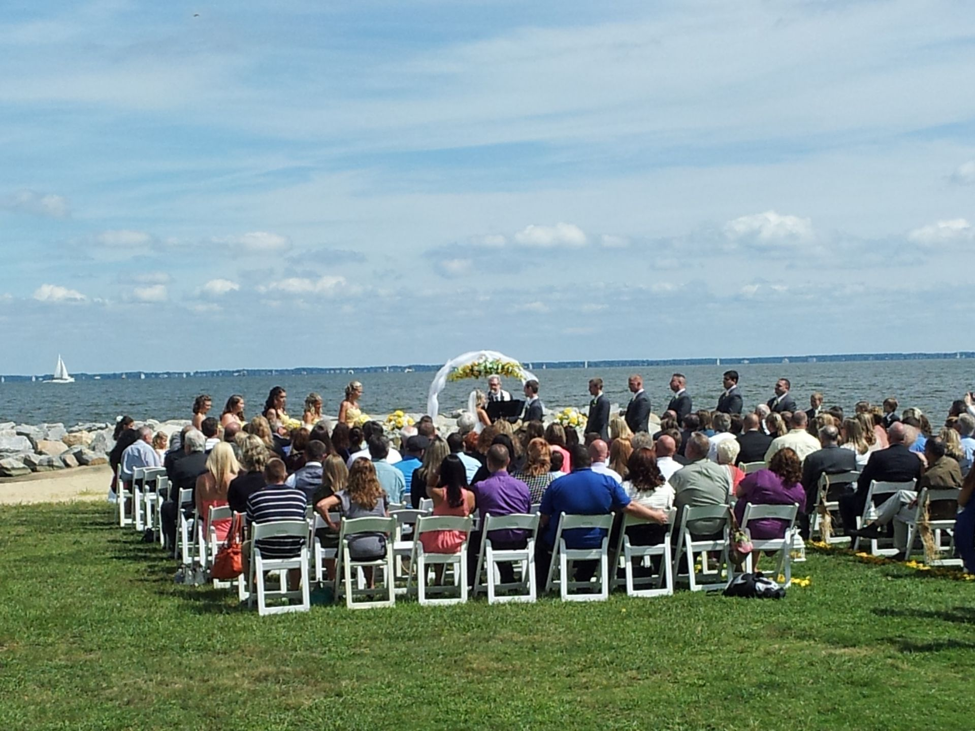 Wedding ceremony with a large group of people taking place outdoors on the grass by the water