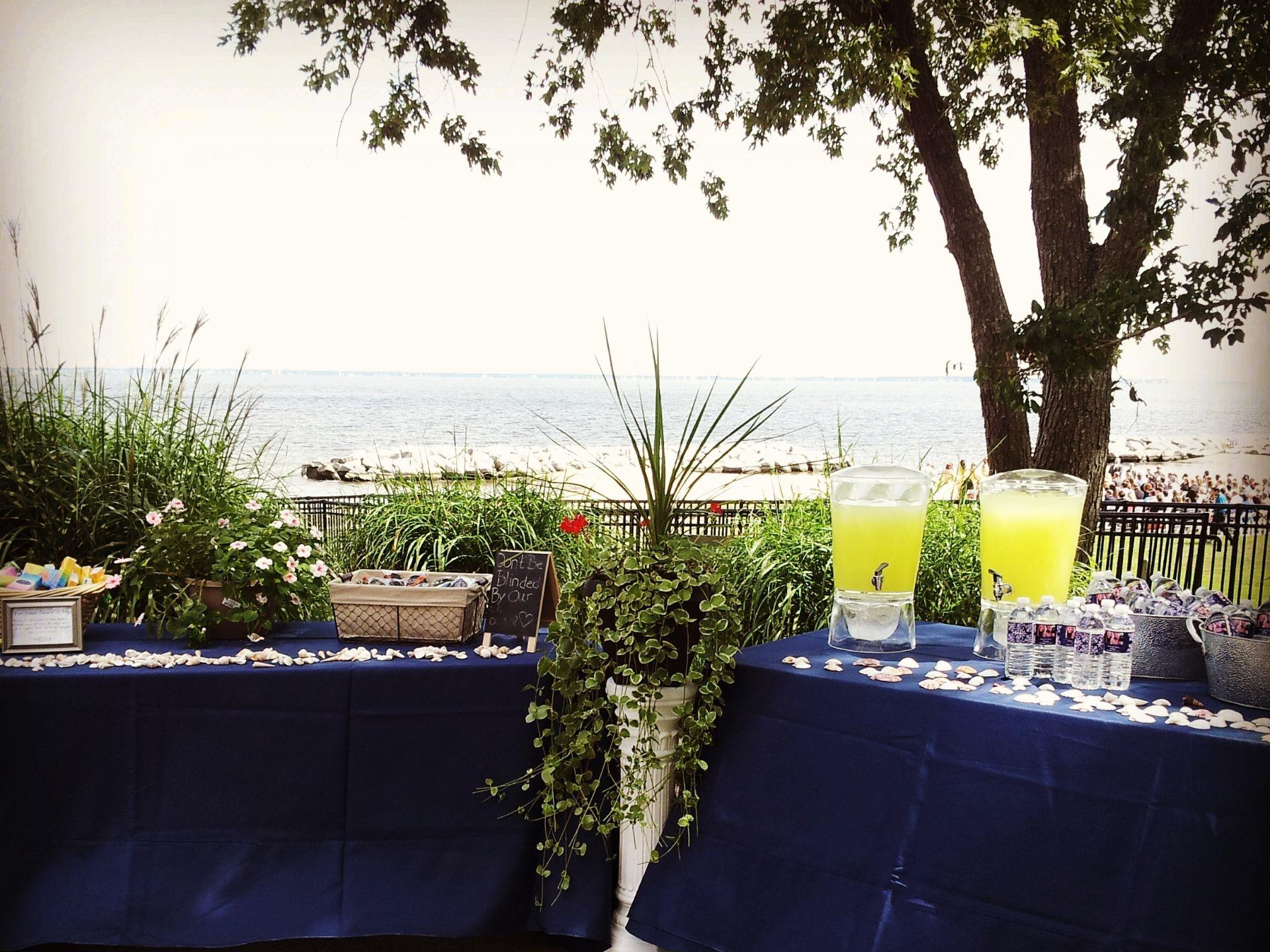 Tables set up with containers of lemonade and a backdrop of a beach