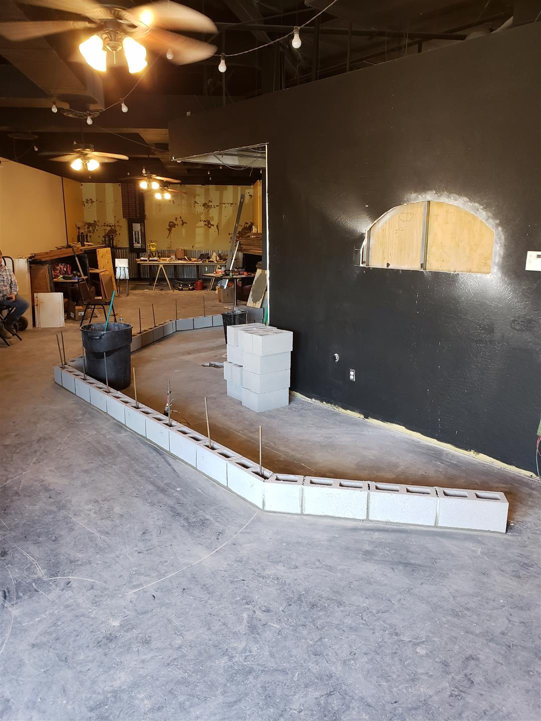interior view of renovations on building - painting walls and laying concrete for floor