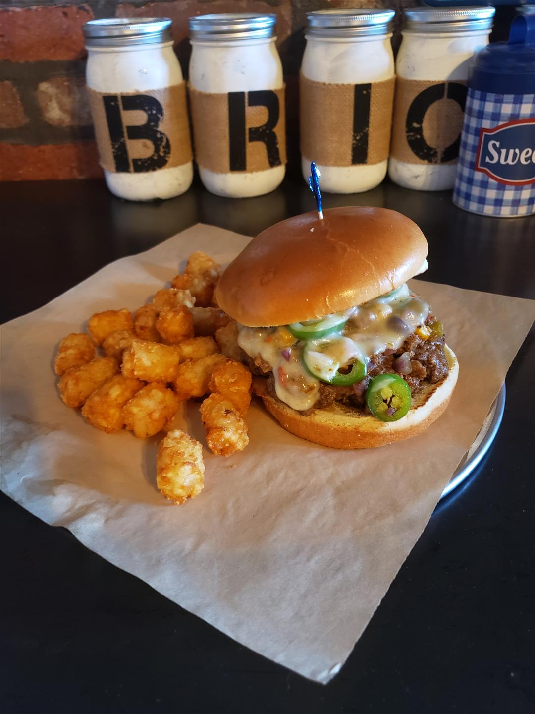 burger with melted cheese and jalapenos with a side of tator tots on a placemat eith the Brickies cans behind them