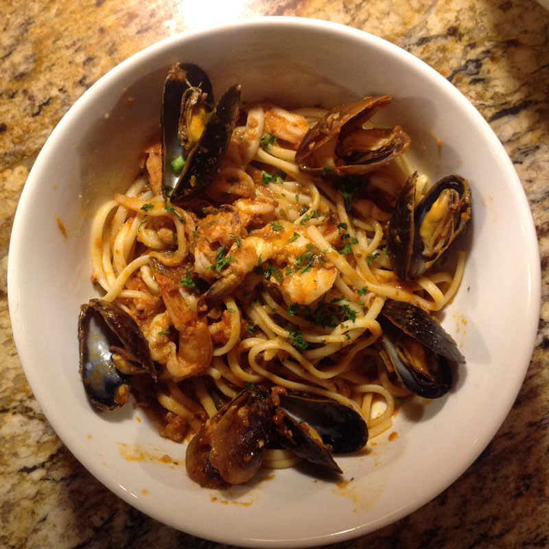 spaghetti topped with mussels and cooked shrimp