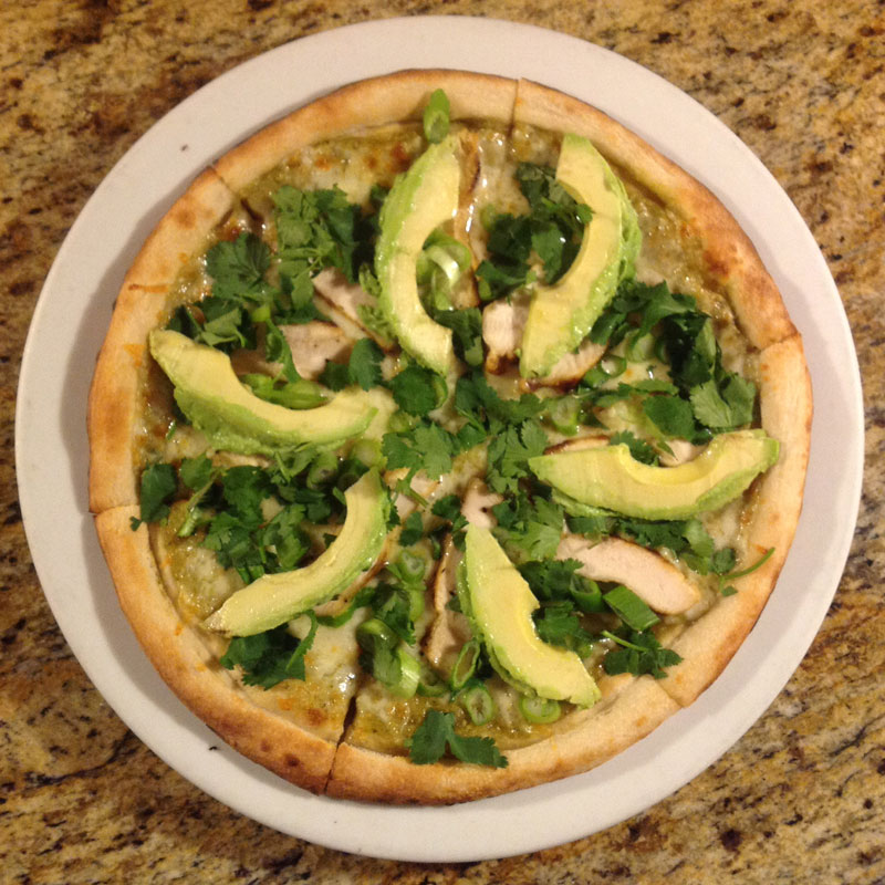 vegetable pizza topped with herbs and avocado