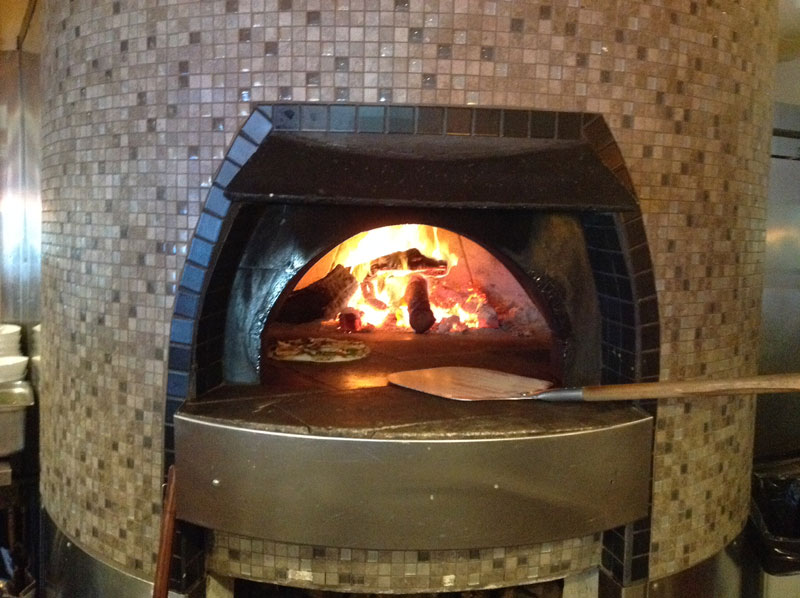 brick oven pizza turned on with a pizza baking inside