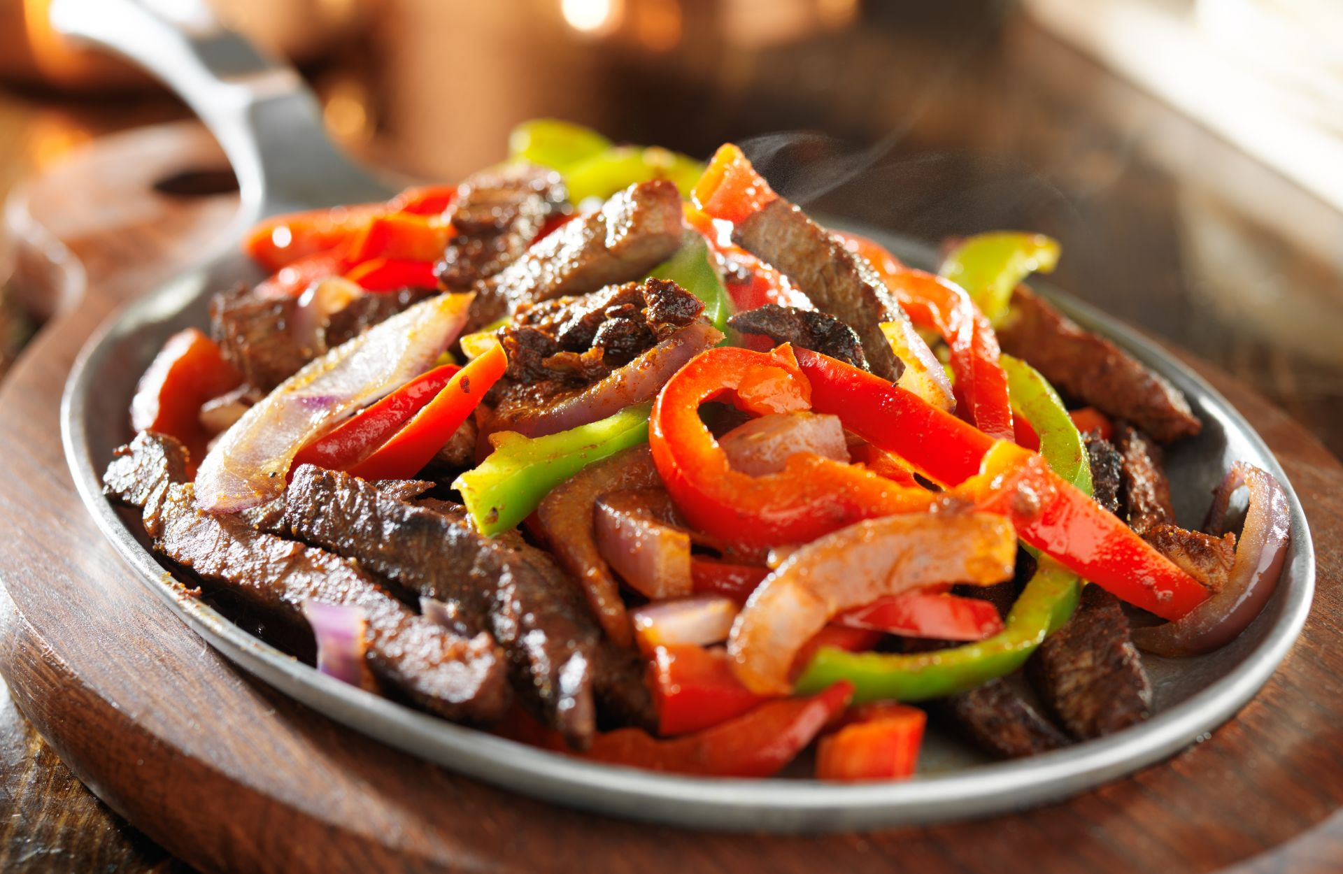 Steak fajitas in a skillet with sauteed peppers and onions