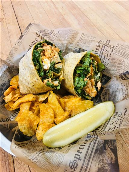 chicken and lettuce in a wrap with french fries and a pickle