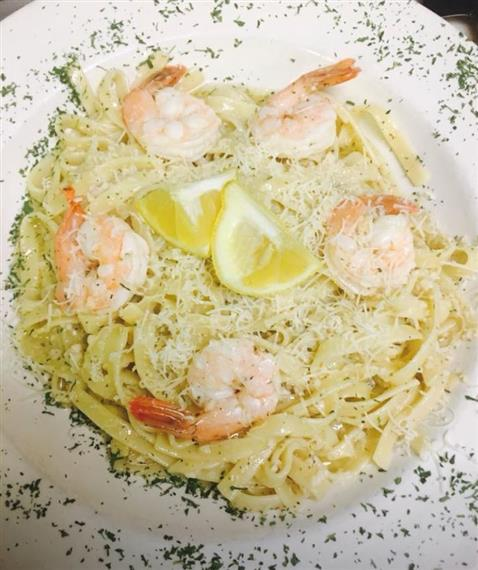 shrimp scampi fish on bed of angel hair pasta and parsley
