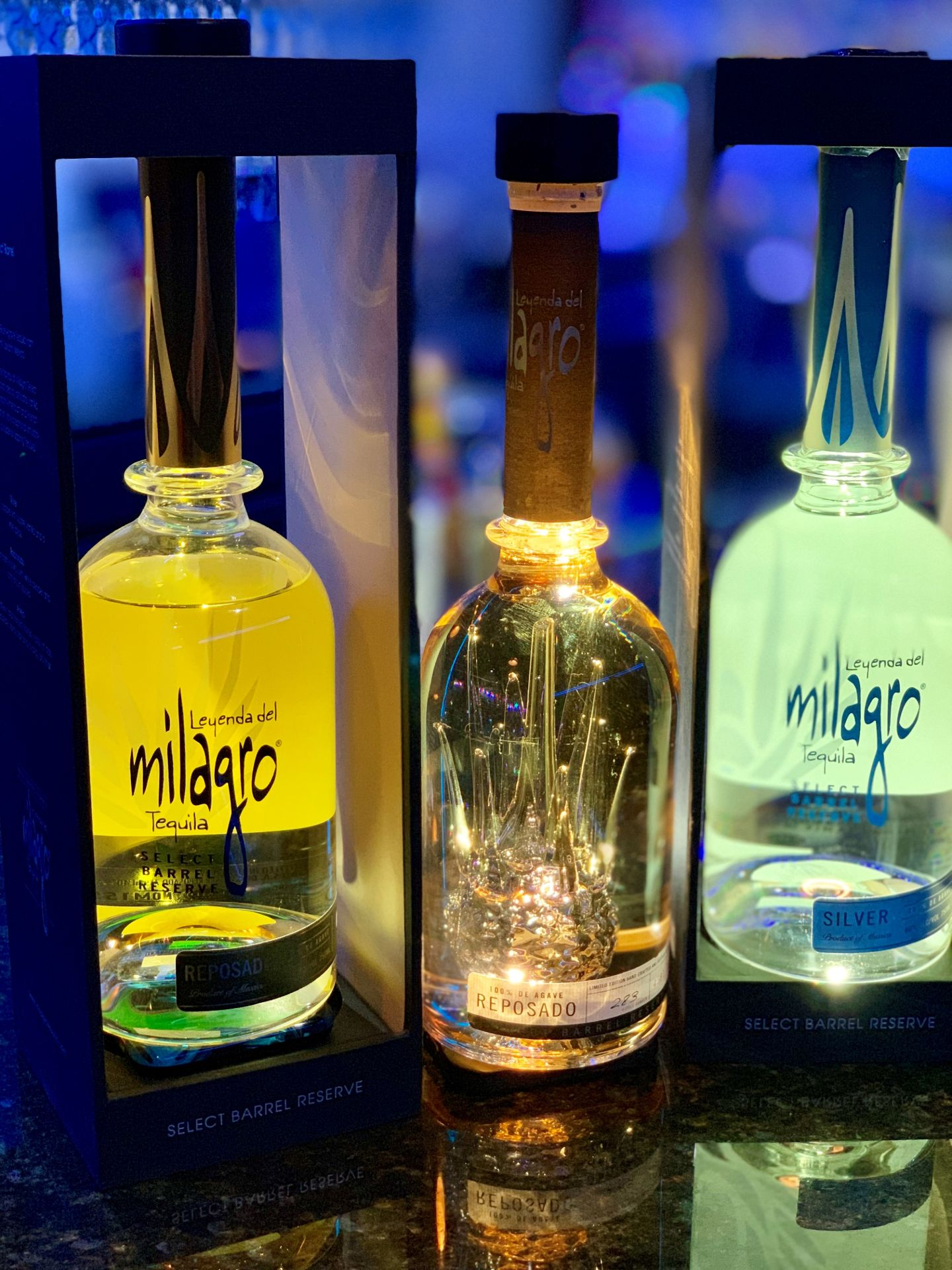 Three bottles of Milagro illuminated on a bar-top