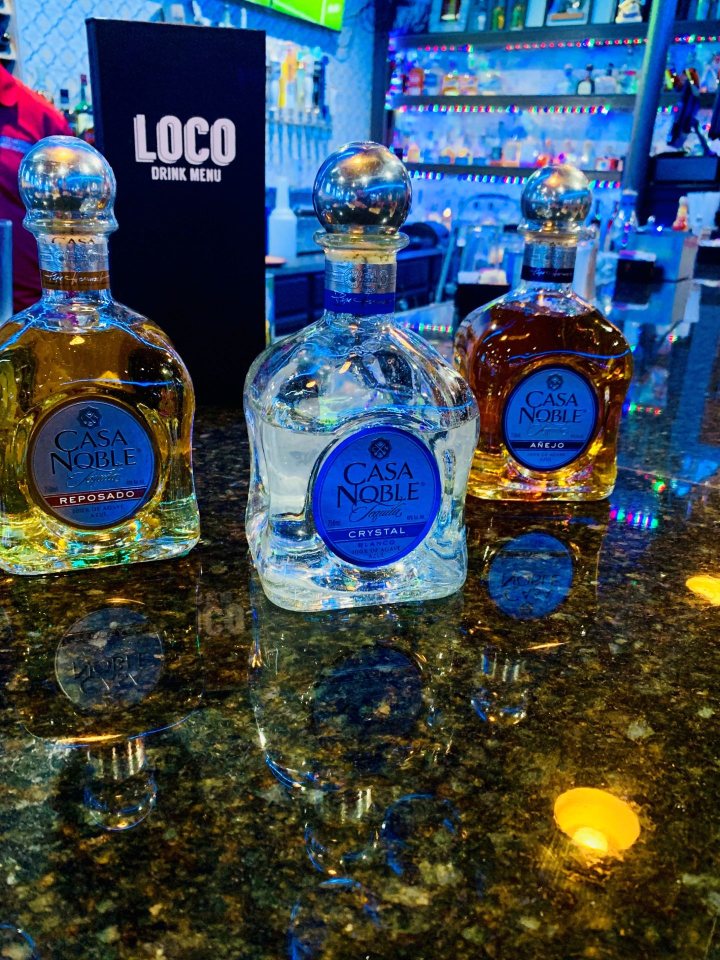 Three bottles of assorted tequila on a bar top in front of a drink menu